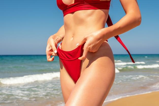 Fille Sexy Mince Avec Une Silhouette Parfaite Dans Un Bikini Rouge Sur La Plage. Photo Premium