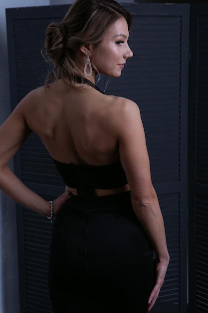 Fille Sexy En Robe Noire Du Soir Se Tient Devant L'écran En Détournant Les Yeux Photo Premium