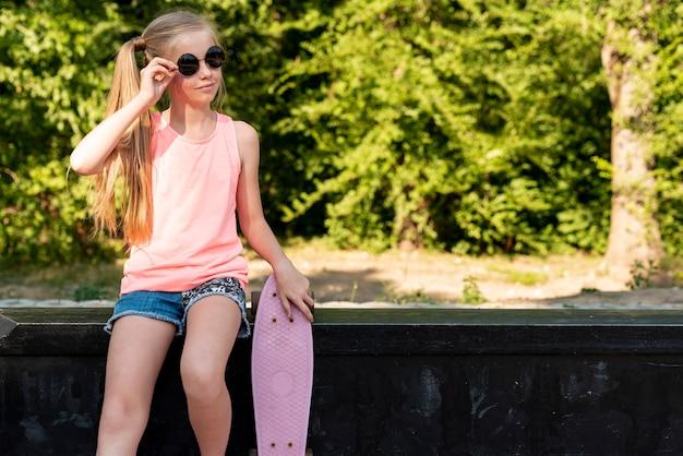 Fille avec skateboard assis sur un banc Photo gratuit