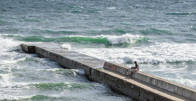 Fille solitaire sur la jetée autour de la mer orageuse Photo Premium