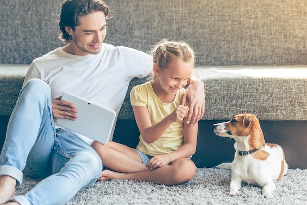 La fille et son beau père jouent avec leur chien. Photo Premium