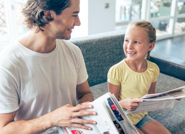La fille et son beau père lisent des journaux. Photo Premium