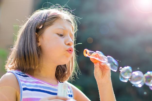 Fille soufflant des bulles de savon dans le parc dans une journée ensoleillée Photo Premium