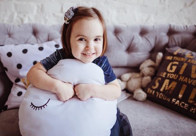 La fille souriante assise sur le canapé Photo gratuit