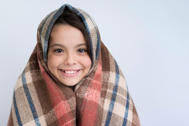 Fille Souriante Avec Couverture D'hiver Photo gratuit