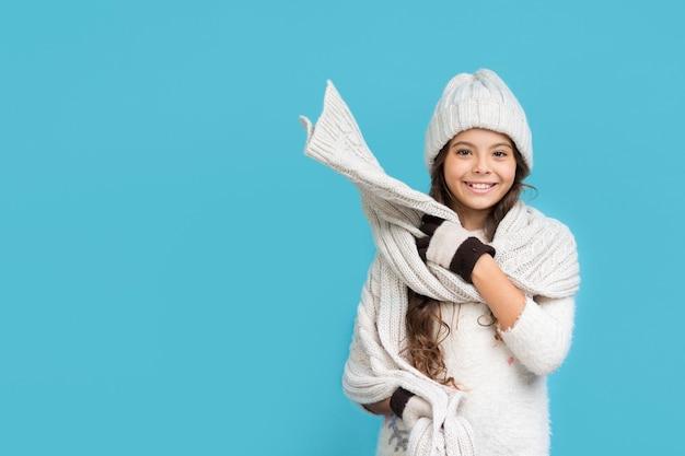 Fille souriante dans l'espace de copie de vêtements d'hiver Photo gratuit