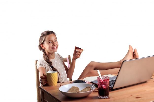 Une fille souriante heureuse avec un visage émotionnel expressif assis à la table avec un ordinateur portable, manger du pain avec de la confiture et tenant une tasse de thé isolé Photo Premium