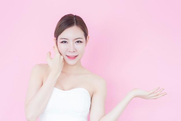 Fille souriante montrant un espace de copie vide présentant votre produit en rose Photo Premium