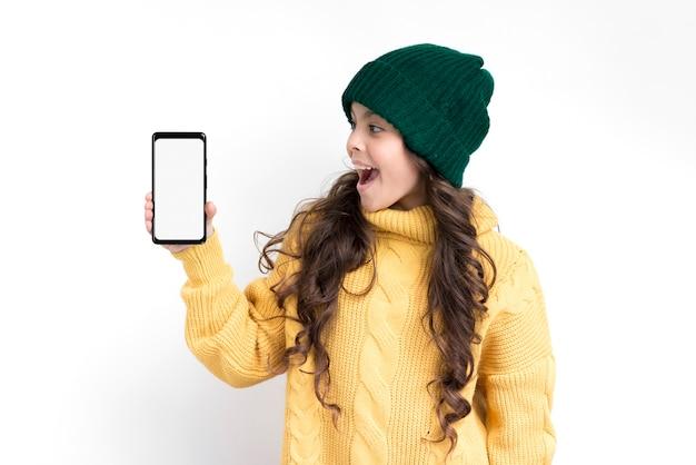Fille souriante tenant le téléphone avec maquette Photo gratuit