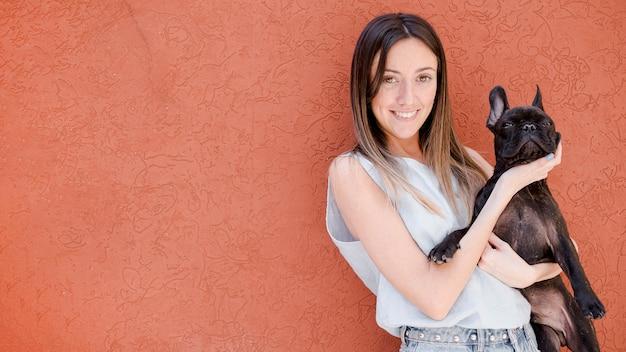 Fille souriante vue de face tenant son chien Photo gratuit