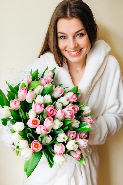 Une Fille Avec Un Sourire Sincère Tient Un Beau Bouquet De Tulipes. Beauté Naturelle. Bouquet De Mariée De Printemps. Joyeuse Journée De La Femme. Photo Premium