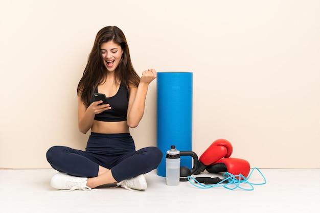 Fille De Sport Adolescent Assis Sur Le Sol Avec Téléphone En Position De Victoire Photo Premium