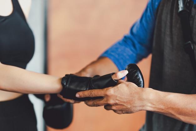 Fille sportive belle femme avec les gants de boxe en arrière au gymnase Photo Premium