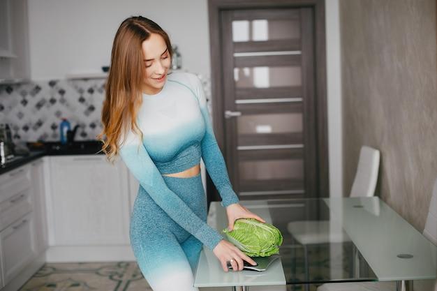 Fille sportive dans une cuisine avec des légumes Photo gratuit