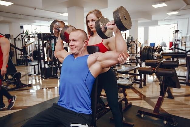 Une fille de sportswear belle et athlétique s'entraînant dans la salle de gym avec un ami Photo gratuit