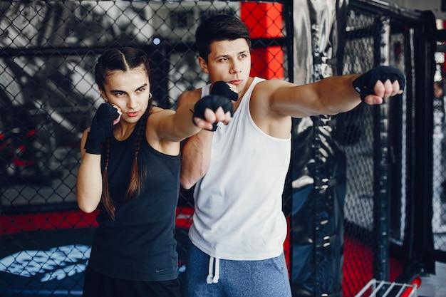 Une fille de sportswear belle et athlétique s'entraînant dans la salle de gym avec son petit ami Photo gratuit