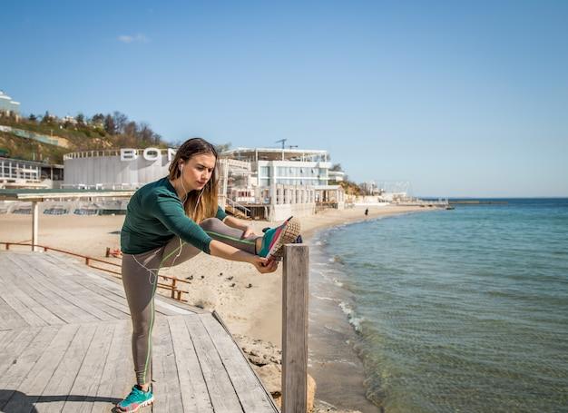 Fille Sportswear Faisant Des étirements Au Bord De La Mer Photo Premium