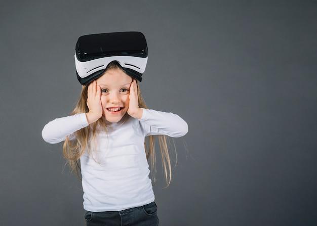 Fille surprise portant des lunettes de réalité virtuelle sur la tête touchant ses joues sur fond gris Photo gratuit
