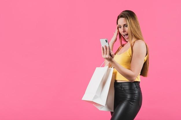 Fille surprise avec des sacs à provisions en regardant téléphone Photo gratuit
