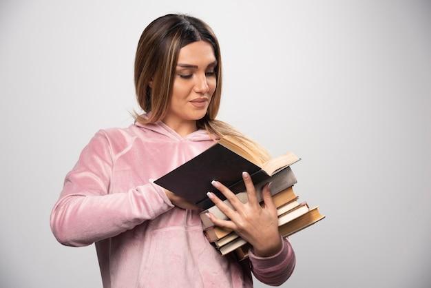 Fille En Swaetshirt Rose Tenant Un Stock De Livres, En Ouvrant Un Sur Le Dessus Et En Le Lisant Photo gratuit