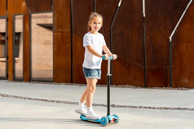 Fille en t-shirt blanc sur scooter bleu Photo gratuit