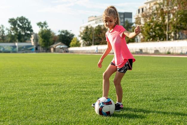 Fille avec un t-shirt rose jouant au football Photo gratuit