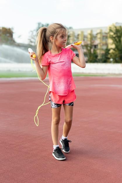 Fille en t-shirt rose avec jumprope Photo gratuit