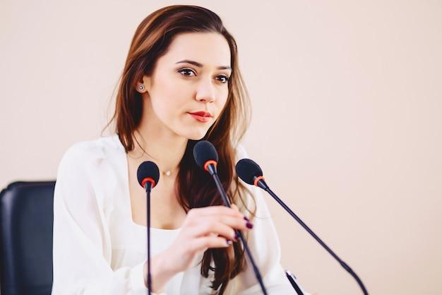 Fille à la table parle au microphone dans la salle de conférence Photo Premium