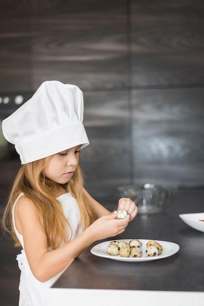 Fille en tablier et chapeau de chef épluchant une coquille d'oeuf de caille Photo gratuit