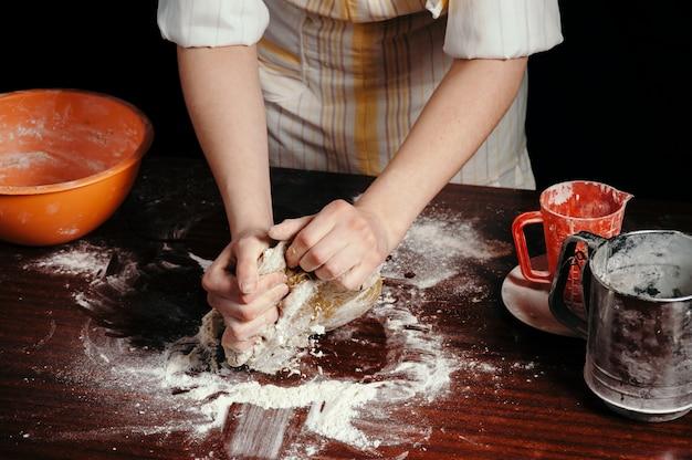 Fille En Tablier Dans La Cuisine Sombre Pétrit La Pâte Avec Ses Mains Sur La Table De Cuisine En Bois Photo Premium