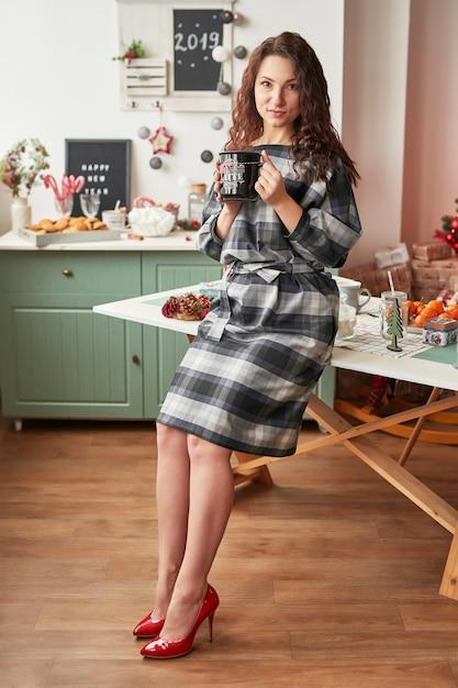 Fille avec une tasse dans la cuisine du nouvel an Photo Premium