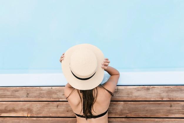 Fille tenant un chapeau à proximité de la piscine Photo gratuit