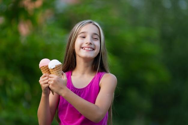 Fille tenant des cornets de glace dans le parc Photo gratuit