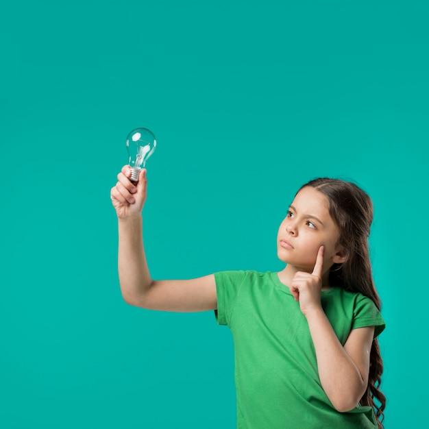 Fille Tenant La Lampe Et La Pensée Photo gratuit