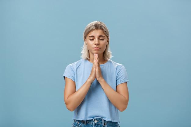 Fille Tenant La Main En Priant Tout En Faisant Voeu, Espérons-le Croire Dieu Entend Ses Prières Avec Les Yeux Fermés Photo Premium