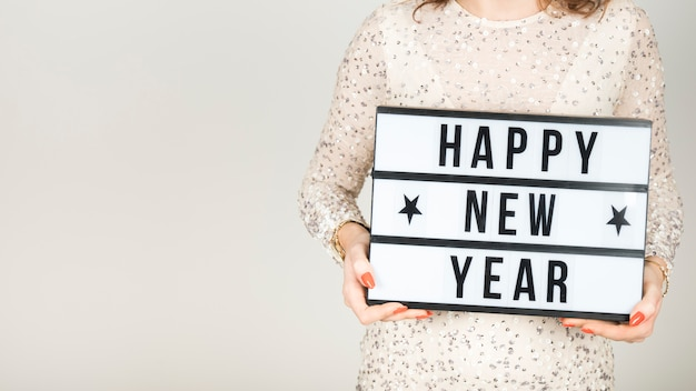 Fille tenant une pancarte de bonne année Photo gratuit