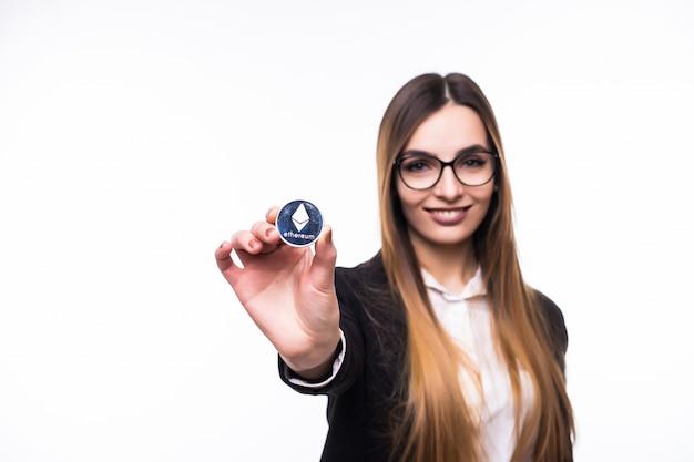 Fille Tenant Une Pièce De Monnaie Ethereum Crypto-monnaie Physique Dans Sa Main Photo gratuit