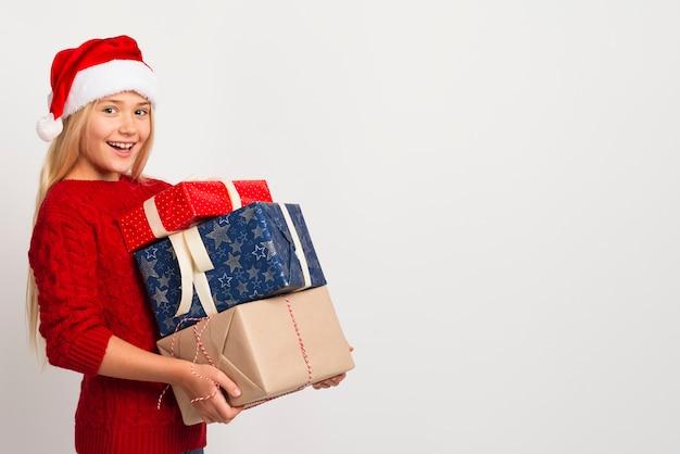Fille tenant une pile de cadeaux Photo gratuit