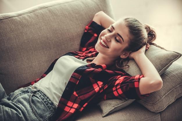 Fille en tenue décontractée est souriant en position couchée sur le canapé. Photo Premium