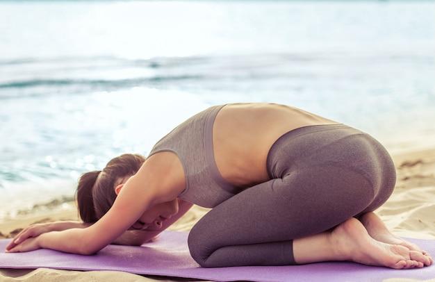 Fille en tenue de sport qui s'étend sur tapis de yoga sur la plage. Photo Premium
