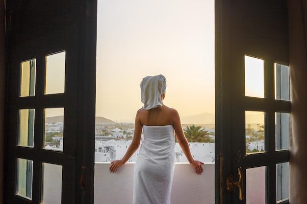 Fille sur la terrasse dans une serviette de bain après la douche regarde le coucher de soleil dans les montagnes Photo Premium