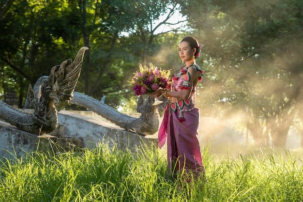 Fille thaïlandaise de belles femmes tenant le lotus de la main en costume traditionnel thaïlandais avec le temple ayutthaya, culture de l'identité de la thaïlande. Photo Premium