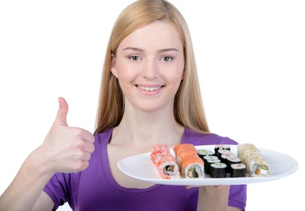 Une fille tient une assiette de somme et montre que le geste est ok. Photo Premium