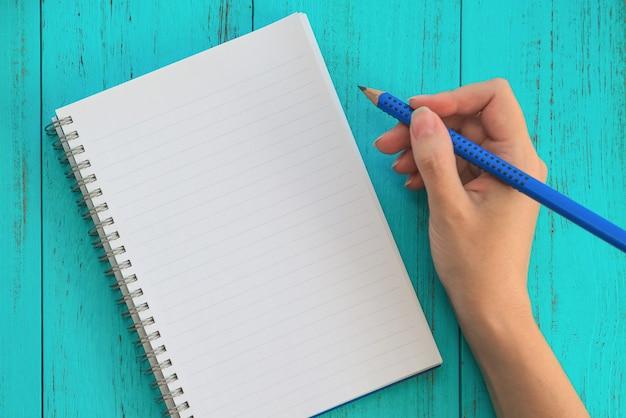 Une fille tient un crayon et se prépare à écrire des objectifs pour l'avenir dans un cahier, une table en bois bleue. Photo Premium