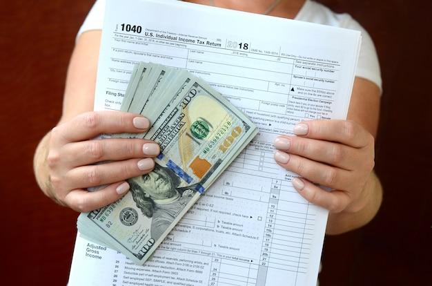 La fille tient dans ses mains le formulaire d'impôt et un grand nombre de billets d'un dollar Photo Premium
