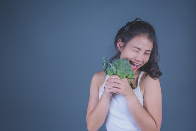 Fille tient les légumes sur un fond gris. Photo gratuit