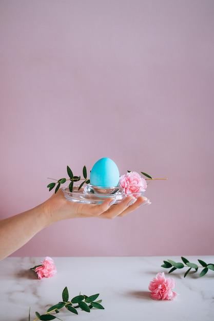 La fille tient un oeuf mangeur bleu sur un support, fond rose et marbre, minimalisme, fleurs Photo Premium