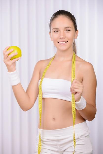 La fille tient une pomme dans ses mains et un centimètre. Photo Premium
