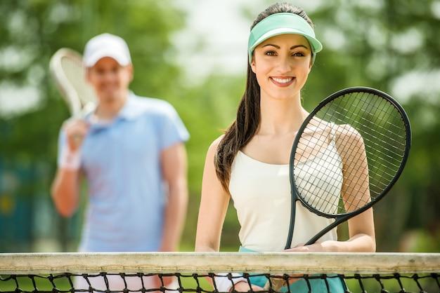 Fille tient une raquette de tennis et sourit. Photo Premium
