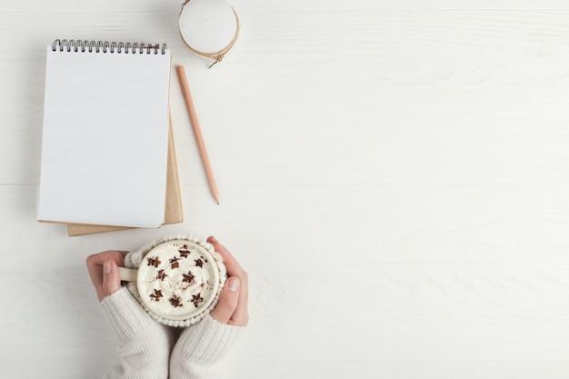 La fille tient une tasse de boisson chaude de l'hiver, avec de la crème fouettée et de la poudre en forme d'étoiles Photo Premium